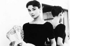 Audrey Hepburn holding up one of her dresses